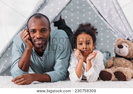 African American Father And Daughter Resting Chins On Hands And Looking At Camera At Home