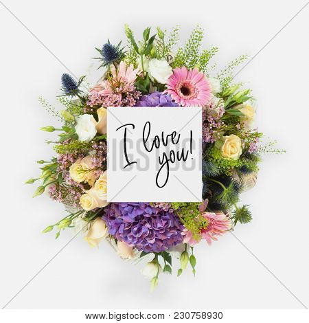 Fresh flowers bunch and card with words i love you written on it