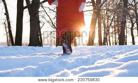 Girl In A Red Down Jacket And Black Felt Boots Walks Through The Snow At Sunset In The Park, Slow Mo