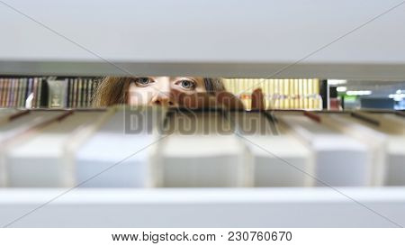 Young Girl Takes A Book From The Bookshelf And Leaves, View Through The Shelves