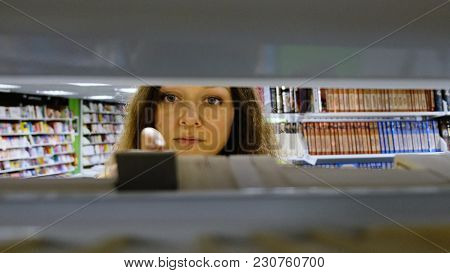 Young Girl Approaches The Bookshelf, Takes The Book And Leaves, The View Through The Shelves