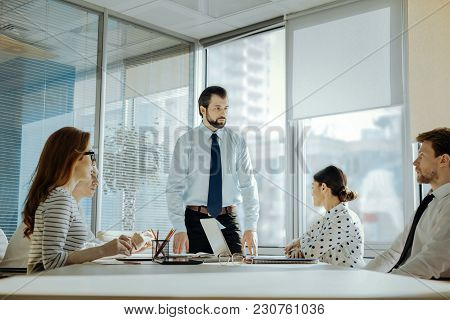 Vital Matters. Handsome Young Man Standing At The Head Of The Table And Conducting A Meeting With Hi