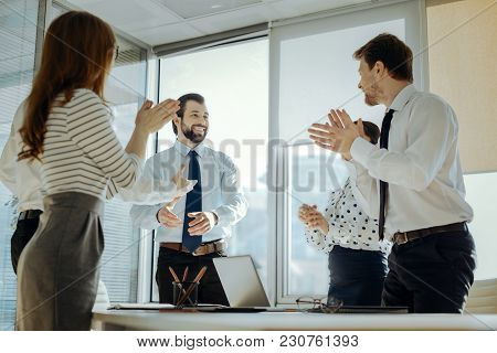 Well Done. Pleasant Upbeat Young Employees Clapping Their Hands And Congratulating Their Colleague W