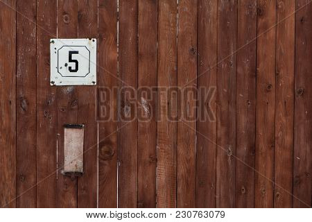 Vintage Grunge Square Metal Rusty Plate Of Number Of Street Address With Number Closeup On The Woode