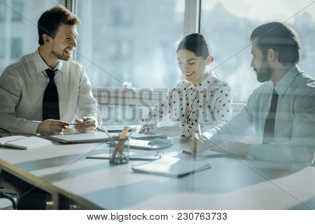 Friendly Ambience. Upbeat Young Colleagues Sitting At The Table Next To Their Boss And Joking Togeth