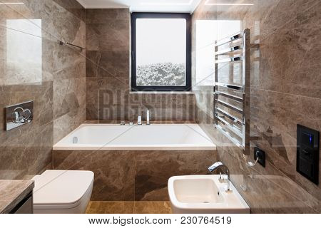 Luxurious marble bathroom with window. Nobody inside