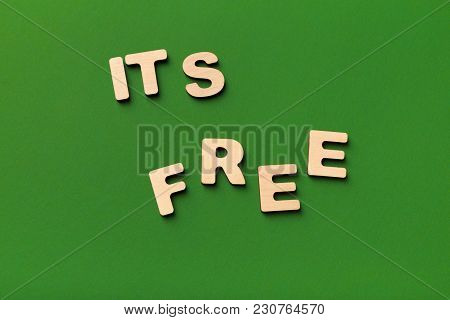 It Is Free Inscription On Green Background. Wooden Letters Phrase, Top View, Copy Space. Ad, Charity