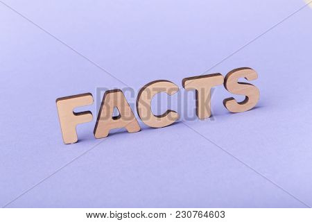 Facts Word Arranged With Wooden Letters On Violet Background. Truth, Reality, Information And Knowle
