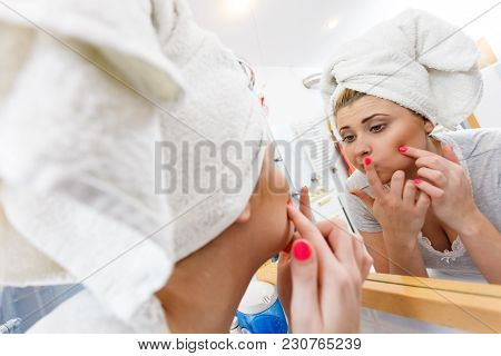 Woman Looking At Her Reflection In Mirror Thinking About Her Complexes Having Serious Face Expressio