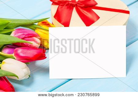 Colorful Spring Tulip Flowers With Decorative Giftbox And Blank Photo On Light Blue Wooden Backgroun
