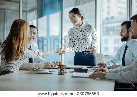 Pleasant Cooperation. Upbeat Young Female Boss Shaking Hands With Her Female Colleague, Congratulati