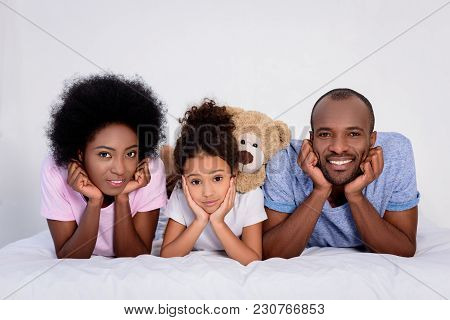 African American Parents And Daughter Resting Chins On Hands At Home