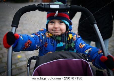 Cute Little Boy Rolls Baby Stroller On The Street. Beautiful Child Smiling And Acting Like An Adult.