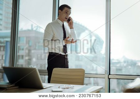 Important Negotiations. Pleasant Business Man Standing Near The Window In His Office And Talking On