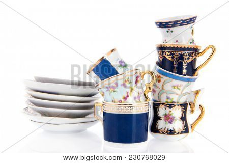 Stacked cups and saucers isolated over white background
