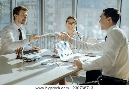 Useful Printouts. Cheerful Young Man Sitting At The Table Next To His Colleagues And Distributing Co