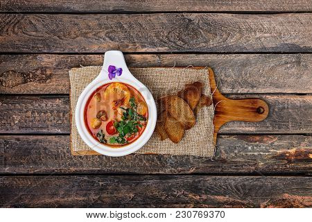 Tom Yam Soup With Prawns And Bread In A White Bowl, Served On The Rustic Cutting Board With A Linen
