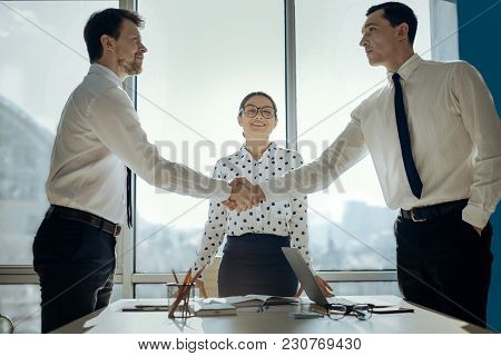 Consensus Is Reached. Handsome Young Businessmen Shaking Hands Having Negotiated A Deal While Their