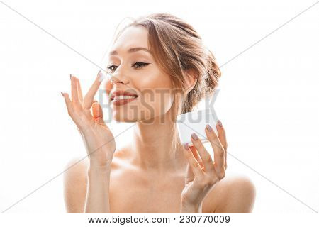 Beauty portrait of half naked pleased woman with soft healthy skin applying face cream isolated over white background
