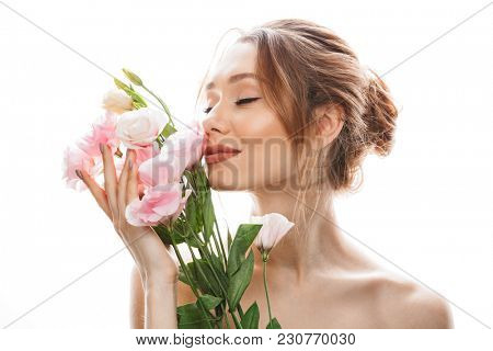 Gorgeous woman 20s with tied auburn hair in bun holding and smelling beautiful eustoma flowers with closed eyes isolated over white background