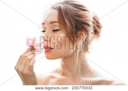 Picture of pretty girl 20s with brown hair in bun and makeup enjoying smell of one eustoma flower isolated over white background poster