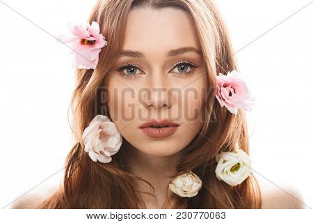 Sensual young woman 20s wearing makeup looking on camera with beautiful eustoma flowers in her long auburn hair isolated over white background