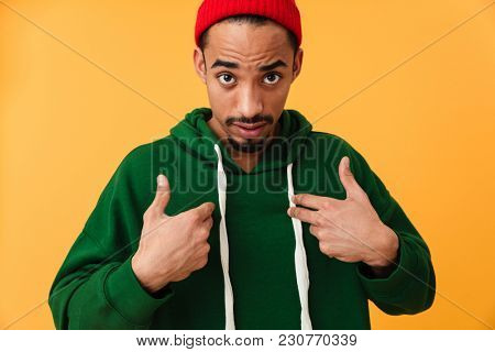 Portrait of a confused young afro american man in hat pointing fingers at himself isolated over yellow background