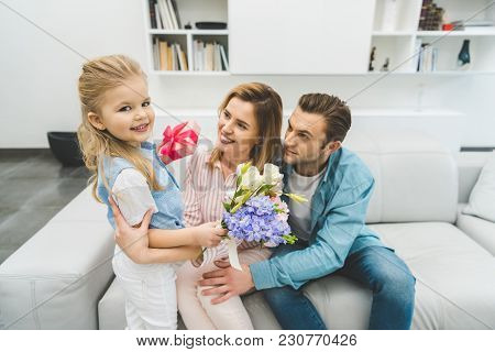 Side View Of Daughter Greeting Smiling Mother With Mothers Day At Home