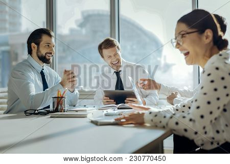 Cheerful Mood. Upbeat Young Colleagues Sitting At The Table In The Conference Room And Laughing At T