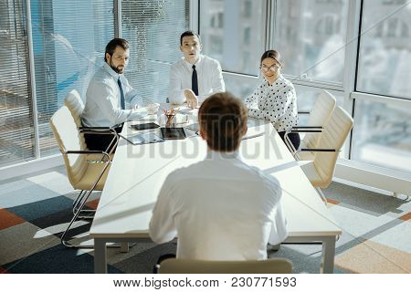 Crucial Meeting. The Back View Of A Young Male Ceo Sitting At The Head Of The Table And Carrying Out
