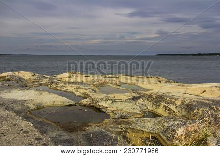 Series Of Tide Pools In Yellow Rocks Near Oregrund, Sweden Under Gray Cloudy Skies