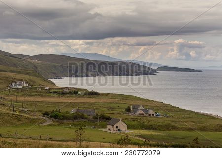 Melvaig, Scotland - June 9, 2012: Landscape Of Loch Ewe Coastline With Green Hills And Houses In Fro
