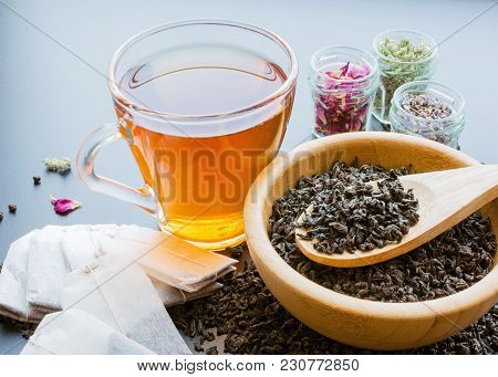 Tea In A Cup, Tea Bags, Herbs And Black Tea Dried Leaves In Wooden Bowl With Spoon