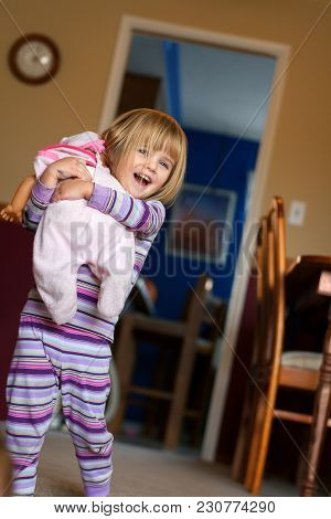 A Happy Little Girl With Blond Hair And Blue Eyes Walks Quickly Towards The Camera Hugging Her Baby