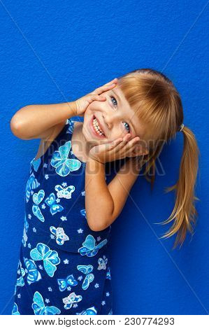 Cute Little Blond Hair, Blue Eyed Girl Holds Her Face In Her Hands With Her Head Tilted To The Side.