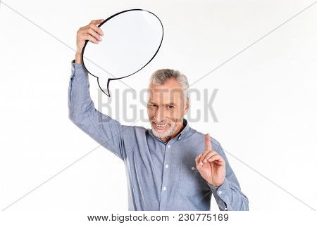 Pleased mature man in blue shirt pointing finger up and holding blank bubble speech isolated