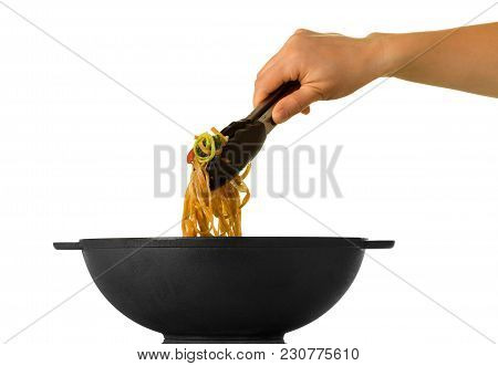 Woman's Hand Takes With Forceps Portion Of Noodles From Pan Wok, Isolated On White