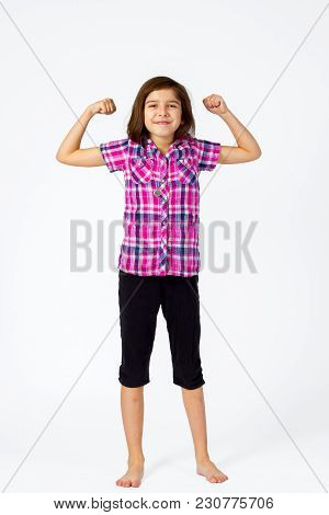 A Young Girl In A Pink, Plaid Shirt Flexes With A Proud Grin On A White Backdrop As She Has Her Port