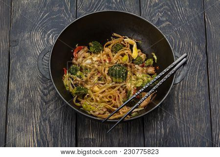 Traditional Asian Dish - Noodles With Meat And Vegetables In Wok, On Wooden Surface