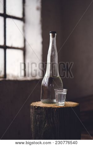 Strong Alcohol Drink In Bottle With Shot Glass In Traditional Rustic Retro Toned Atmosphere