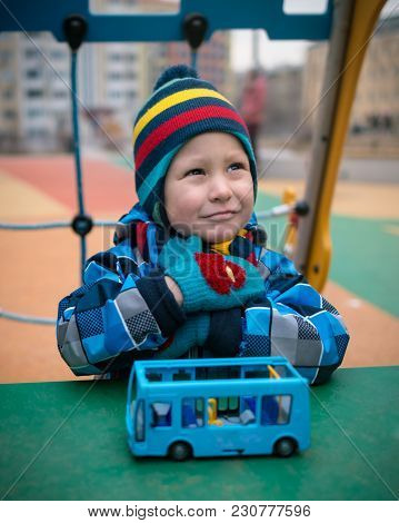 Beautiful Child On The Playground Area In The Winter. Pensive Little Boy Sits In Front Of A Toy And