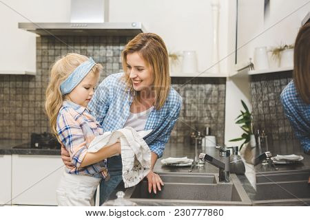 Portrait Of Smiling Mother Hugging Daughter While Washing Dishes After Dinner At Home