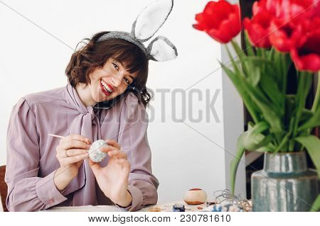 Beautiful Stylish Girl In Bunny Ears Smiling And Painting Easter Eggs On Rustic Table With Colorful