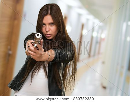 Portrait Of A Woman Holding Gun in a passage way
