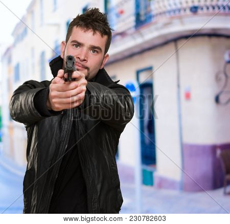 portrait of a man pointing with a gun, outdoor