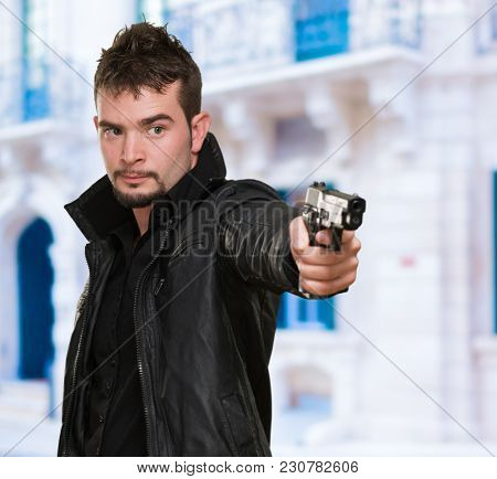 handsome man pointing with gun, outdoor