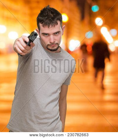 mad man pointing with gun at a city by night