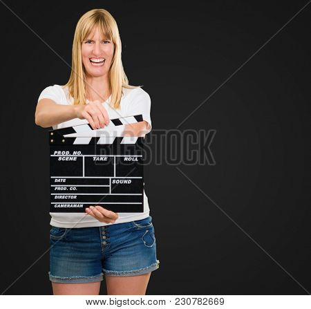 Happy Woman Holding Clapper Board against a black background