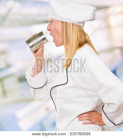Female Chef Holding Tin Shouting  in a profesional kitchen