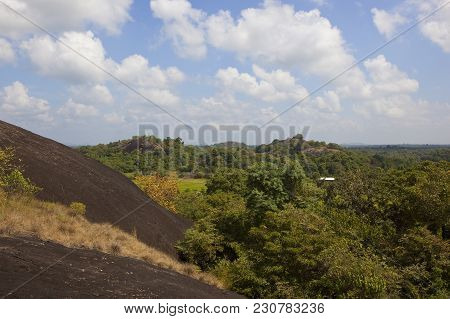 Volcanic Rock Formation At Wasgamuwa National Park In Sri Lanka Under A Blue Sky With Fluffy White C